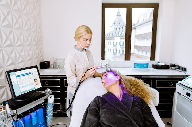 Young woman getting face skin phototherapy treatment by blue light in modern cosmetology clinic. young blond woman cosmetologist doing blue light facial treatment on face skin