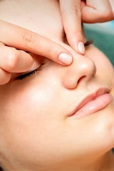 美容院で美容師が目を閉じてフェイシャルマッサージを受ける若い女性