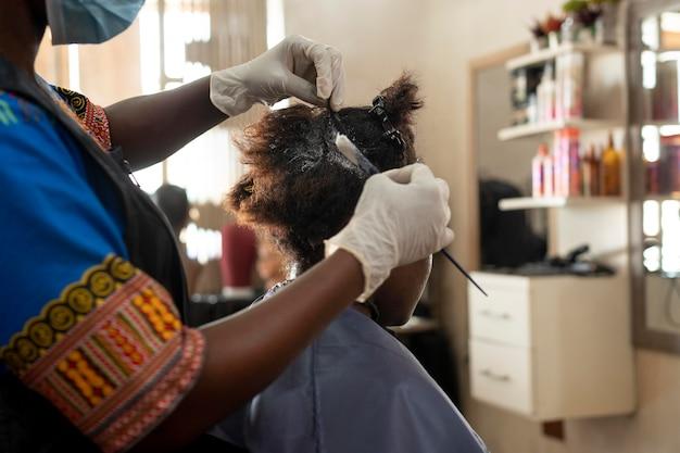 살롱에서 그녀의 머리를 받고 젊은 여자