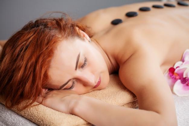 Молодая женщина, получающая массаж горячими камнями в спа-салоне.