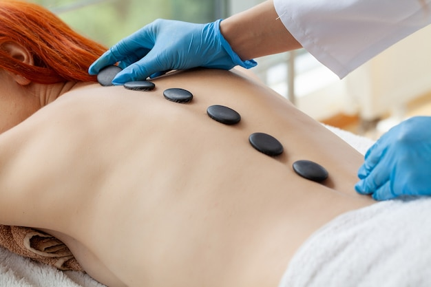 Young woman getting hot stone massage in spa salon.