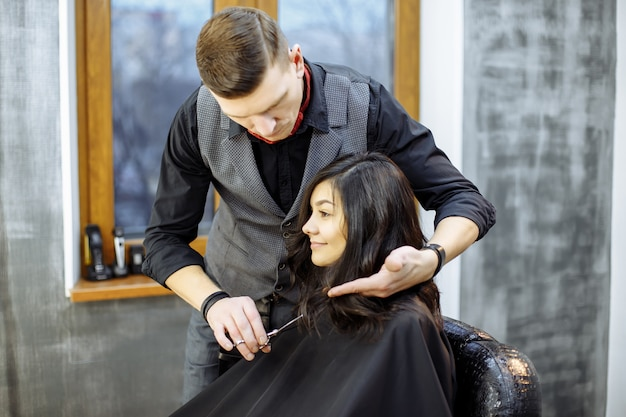 Young woman getting a new haircut at hairdressing salon.