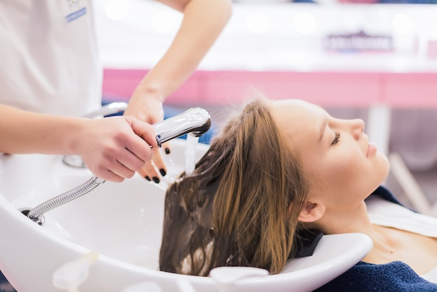 전문 헤어 스타일링 살롱에서 새로운 헤어 스타일을 받고 젊은 여자. 미용사가 머리를 마사지하고 있습니다.