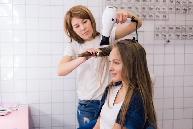 Young woman getting new hairstyle with dryer at professional hair styling saloon.