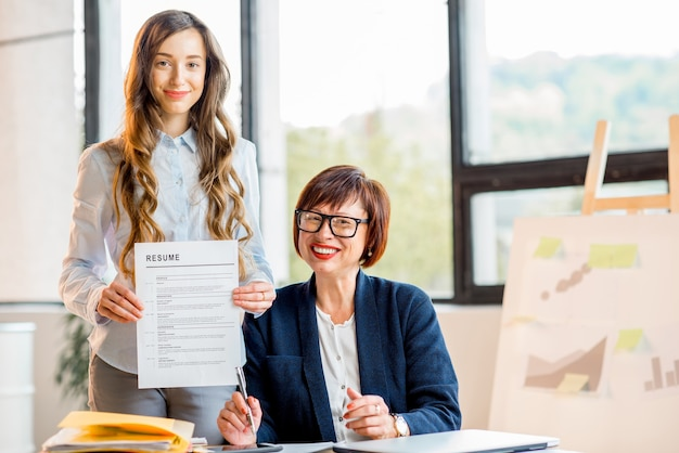 Young woman getting a new job holding resume at the office with older woman
