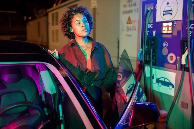 電気自動車から降りて充電してもらう若い女性