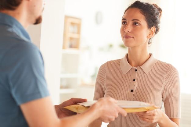 Молодая женщина получает посылки от курьера, у нее есть доставка домой