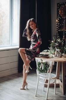 Молодая женщина готовится встретить новый год дома