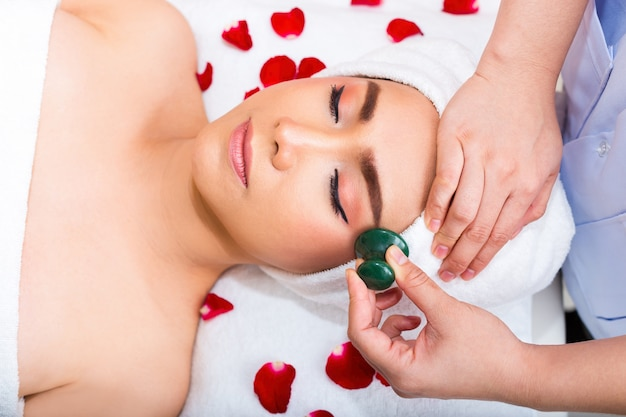 若い女性の美容スパサロンでスパマッサージ治療を取得