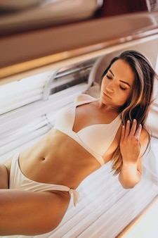 ソラリウムで日焼けする若い女性
