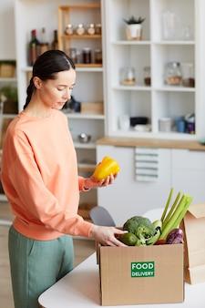 Молодая женщина получает коробку со свежими овощами, она стоит на кухне и распаковывает его