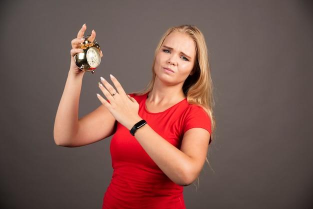 暗い壁に時計で疲れている若い女性。