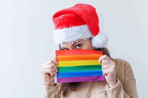 Lgbtの虹色の旗と赤いサンタクロースの帽子の若い女性の女の子