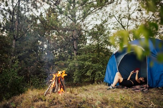 焚き火の近くのテントに横たわって、夏の日に本を読んでいる若い女性の女の子の旅行者。