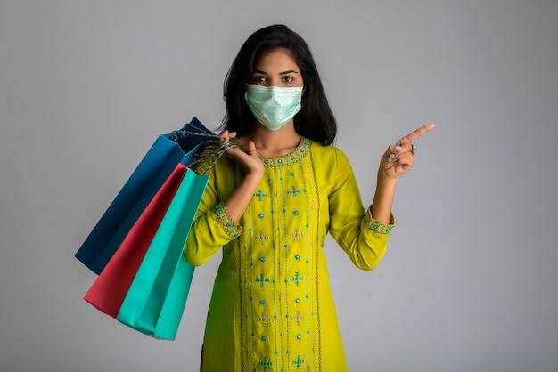 Young woman girl wearing medical mask holding shopping bags on grey background. shopping discount sale concept.