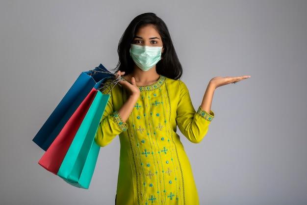 灰色の背景に買い物袋を保持している医療マスクを身に着けている若い女性の女の子。ショッピング割引セールのコンセプト。