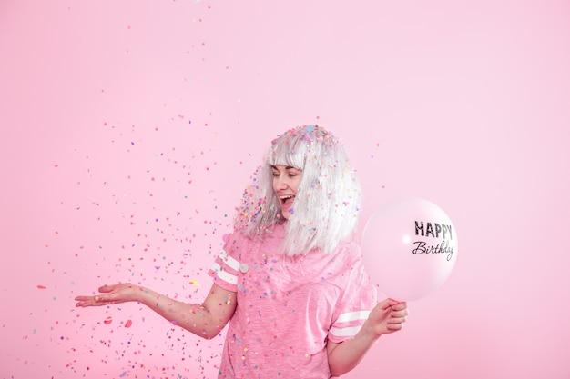 Giovane donna o ragazza con palloncini buon compleanno. lancia coriandoli dall'alto. concetto di festa e festa.