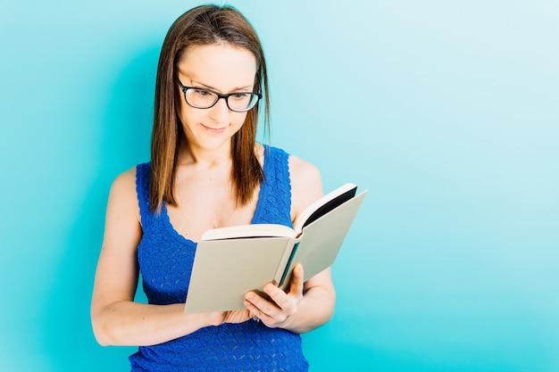 Молодая женщина-девушка с синим фоном, читающая книгу в очках и место для копии