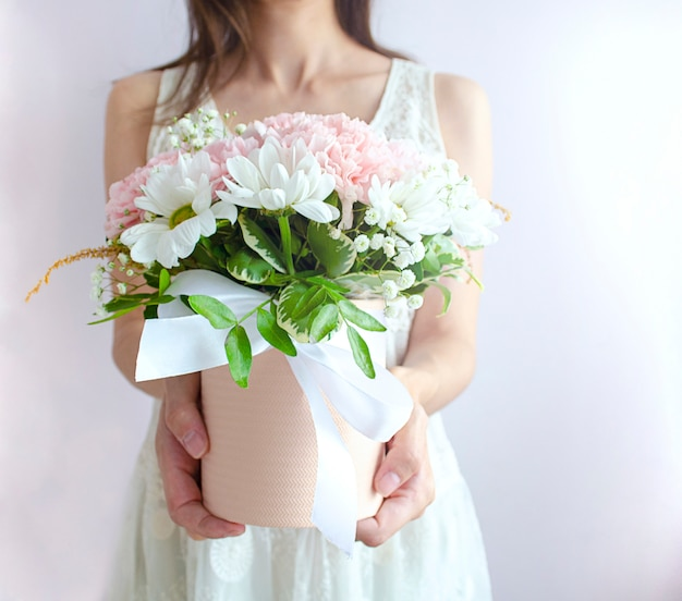 Молодая женщина дает букет цветов в корзине. невеста с букетом цветов в белом свадебном платье на светлом фоне.