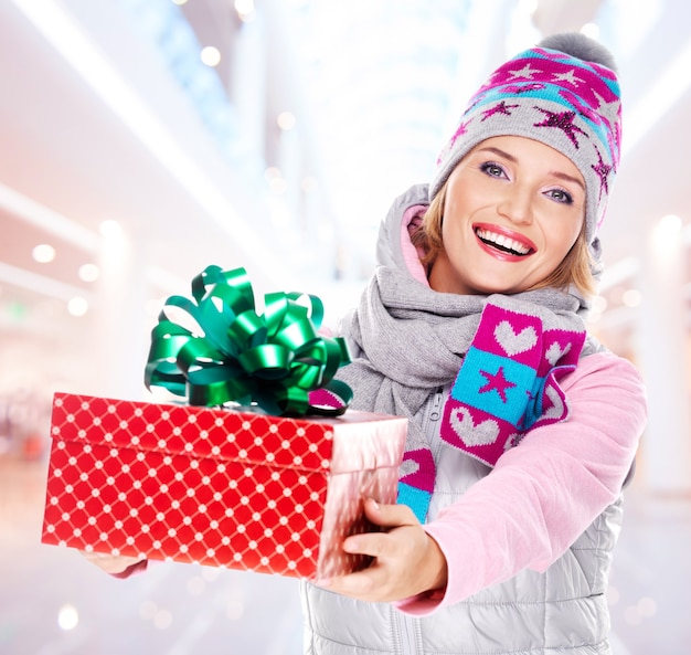 Молодая женщина дарит рождественский подарок одетая в зимнюю верхнюю одежду