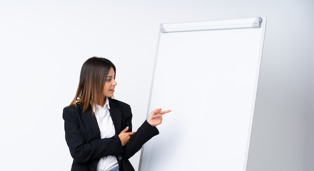 ホワイトボードでプレゼンテーションを行い、それを指している若い女性