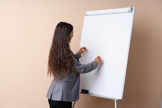 ホワイトボードでプレゼンテーションを行い、それを書く若い女性