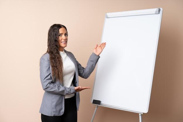 ホワイトボードにプレゼンテーションを行う若い女性