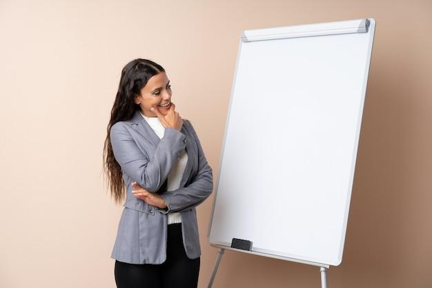 サイドを探しているホワイトボードでプレゼンテーションを行う若い女性