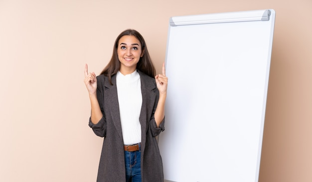 素晴らしいアイデアを指しているホワイトボードでプレゼンテーションを行う若い女性