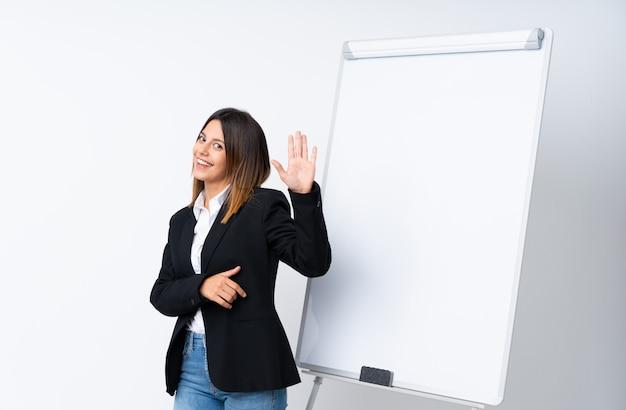 幸せな表情で手で敬礼ホワイトボードにプレゼンテーションを行う若い女性