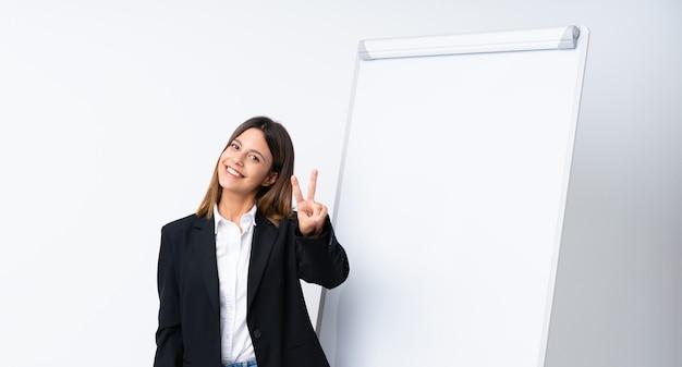 笑顔と勝利のサインを示すホワイトボードでプレゼンテーションを行う若い女性