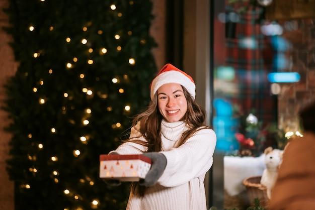 겨울 거리 선물 교환 개념에 야외 당신을 위해 상자를주는 젊은 여자.