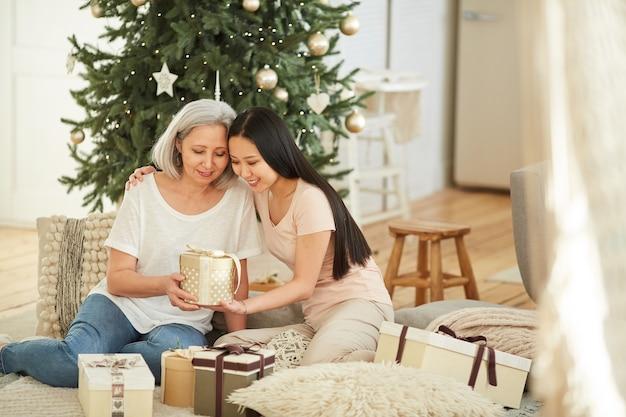 Молодая женщина дарит рождественский подарок своей матери, сидя на полу дома в канун рождества