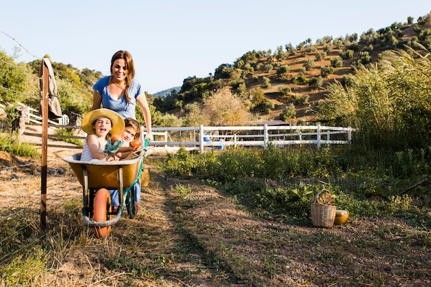 Young woman giving mother and daughter a ride in wheelbarrow at field