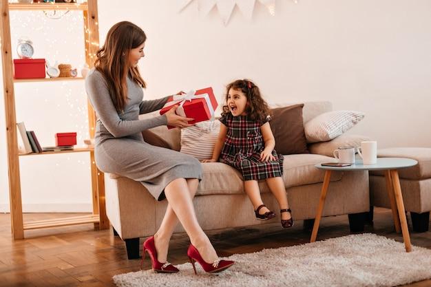 딸에게 선물을주는 젊은 여자. 엄마와 아이가 휴가에 선물 포즈.