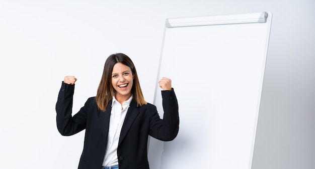Young woman giving a presentation on white board celebrating a victory