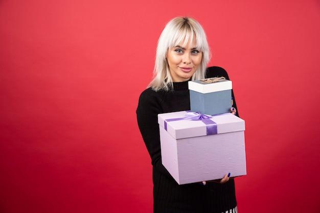 Giovane donna che dà i regali su una parete rossa.