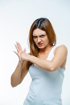 Молодая женщина дает кулаком ее ладонь и выглядит агрессивно