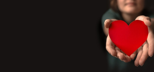 Young woman giving red heart. concept of giving love. healthcare, life insurance, mental health banner. black background, banner with copy space photo