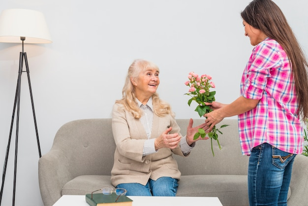Young woman giving rose bouquet to her senior mother sitting on sofa at home