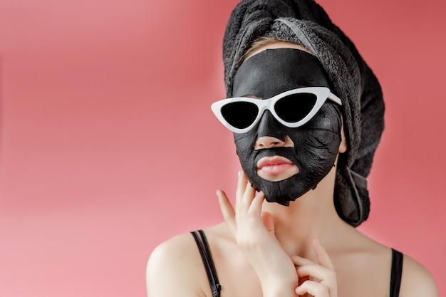 Young woman in glasses appling black cosmetic fabric facial mask. face peeling mask with charcoal, spa beauty treatment, skincare, cosmetology. close up
