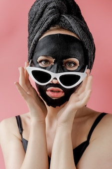 Young woman in glasses appling black cosmetic fabric facial mask on pink background. face peeling mask with charcoal, spa beauty treatment, skincare, cosmetology. close up