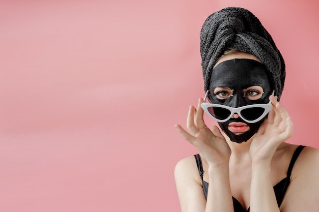 Young woman in glasses appling black cosmetic fabric facial mask on pink background.