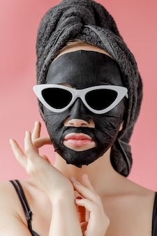 Young woman in glasses apply black cosmetic fabric facial mask on pink wall. face peeling mask with charcoal, spa beauty treatment, skincare, cosmetology. close up