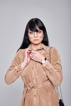 Young woman in glasses, elegant brown dress. girl posing on a grey wall. hairstyle. girl with black handbag. fashion photo