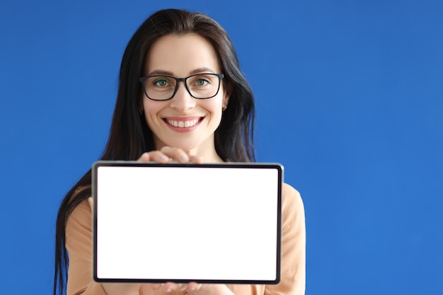 Young woman in glasses holding digital tablet with white screen in her hands