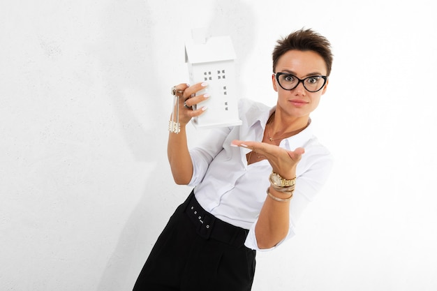 Young woman in glasses holds a house model and keys on white