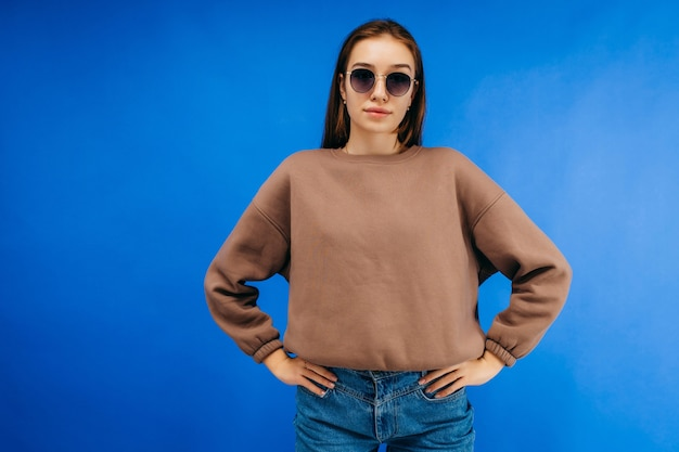 Young woman in glasses and hoodie posing in studio on blue background