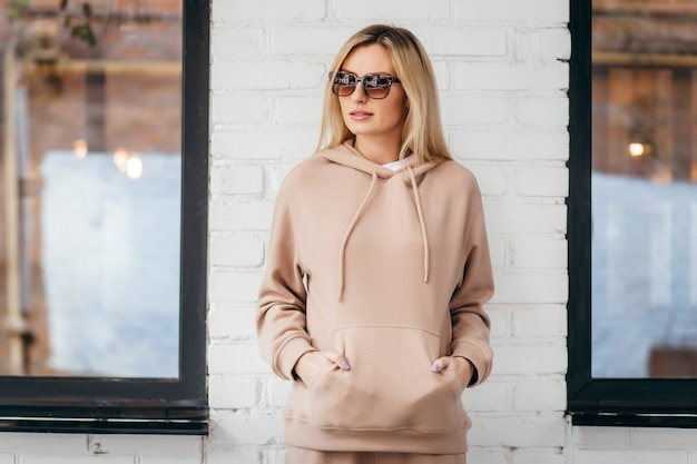 Young woman in glasses and hoodie