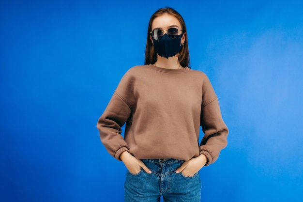 Young woman in glasses, medical mask and hoodie posing in studio on blue background